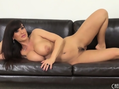 Lisa Ann gets on the floor to toy and back on the sofa to pose